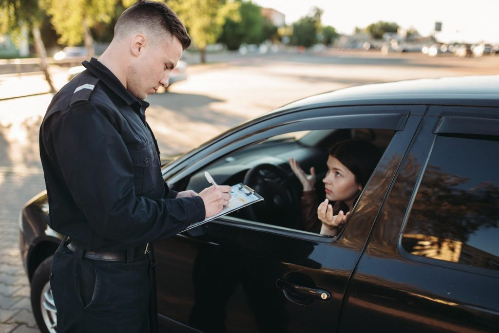 Cop issues a traffic ticket to a young girl as she waits in her car for him to finish.